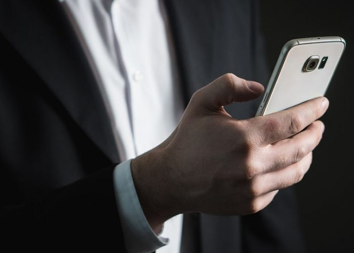 Man in suit holding mobile phone in hand