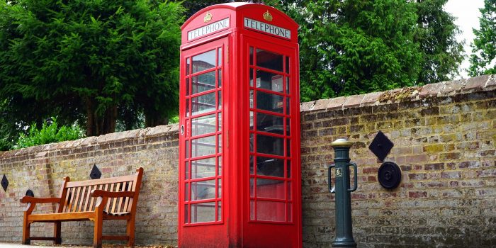 Red phonebox booth next to a stone wall with a park bench nearby